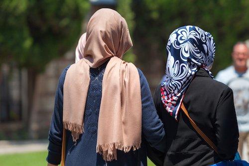 Backs of two women in headscarfs walking in the park